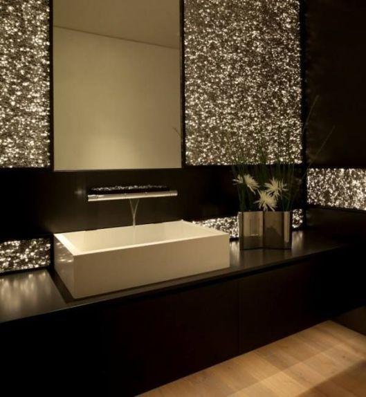 pops of metallic wallcovering enhance a streamlined restroom