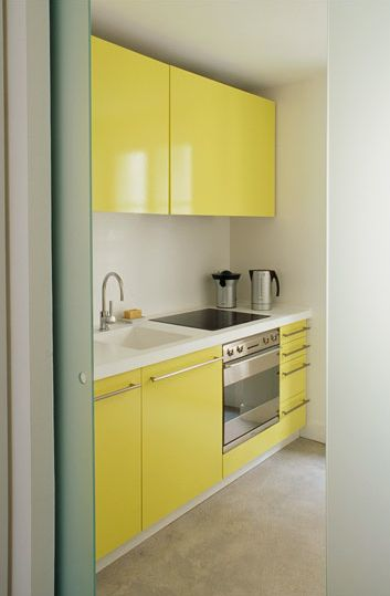 bright, high gloss yellow is   the perfect pop for this small, streamlined kitchen
