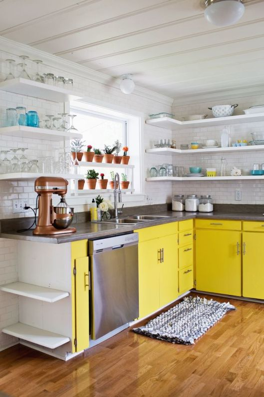 this kitchen has a retro vibe with bright yellow base cabinets and  open white shelving above
